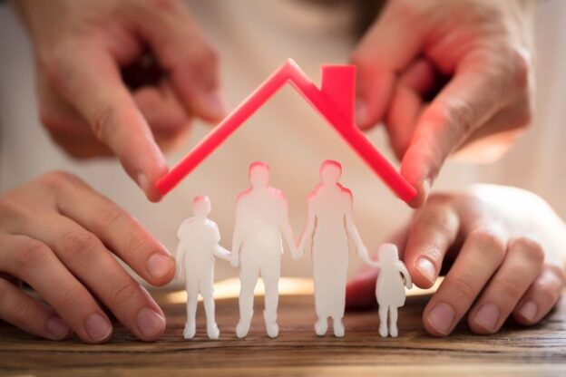 Two People Protecting Family Figures With Red Roof Over Wooden Desk